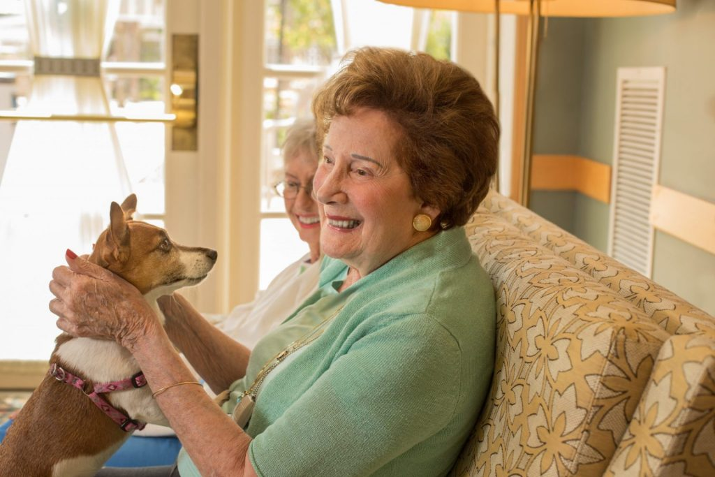 Two female residents smiling holding a dog