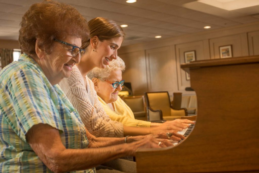Residents and young lady playing piano together
