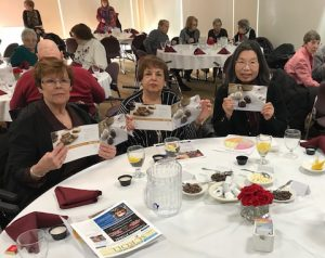 """attendees at a """"Jews and Chocolate"""" event sitting at dining tables"""