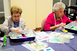 Two residents painting in art class at Ring House
