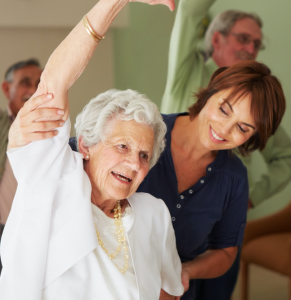 woman assisting an older woman in a stretch pose
