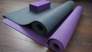 two partly rolled yoga mats, turquoise and purple, a purple yoga block