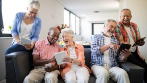 Senior Living Residents Using Digital Devices on Couch