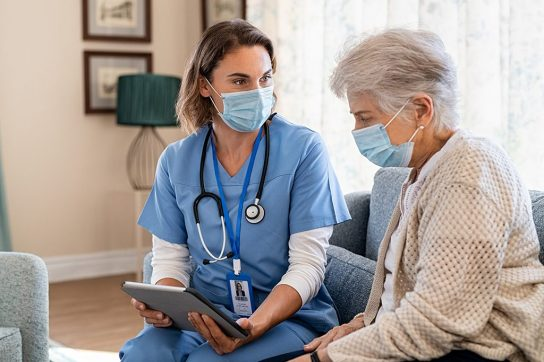 Nurse chatting with senior woman, both are wearing masks.